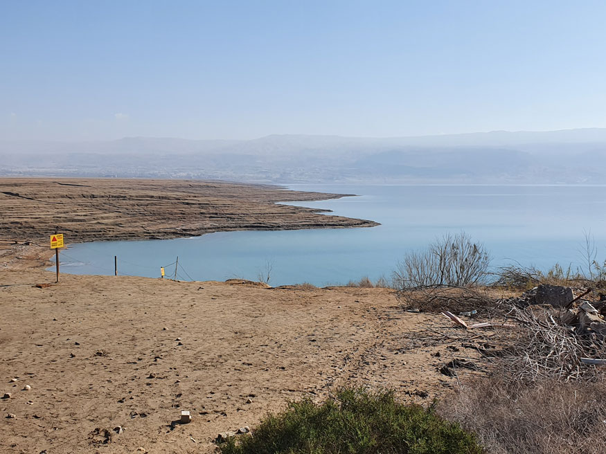 Deniz seviyesinden 420 metre aşağıda olan Lut Gölü (Ölü Deniz). Sarı tabela mayın uyarısı yapıyor. Gölün karşı tarafı Ürdün toprakları.