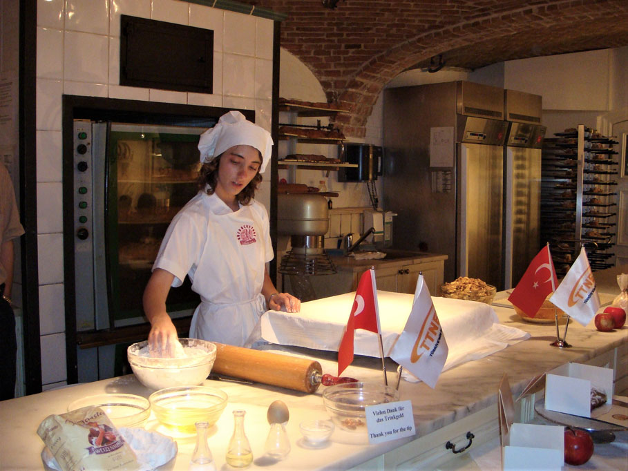 Bu aşçı kız, Avusturya'nın milli tatlısı Apfelstrudel'in, yani Elmalı Turta'nın yapımını uygulamalı olarak gösteriyor