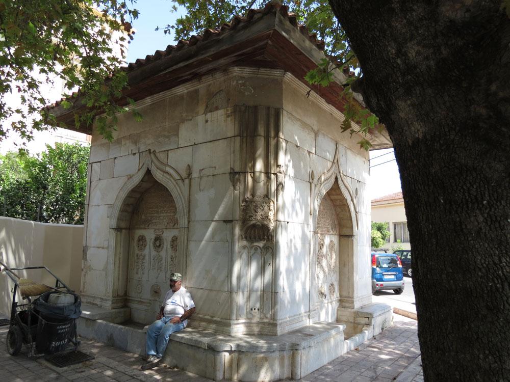 Osmanlı eseri çeşme ve gölgesinde dinlenen temizlik işçisi