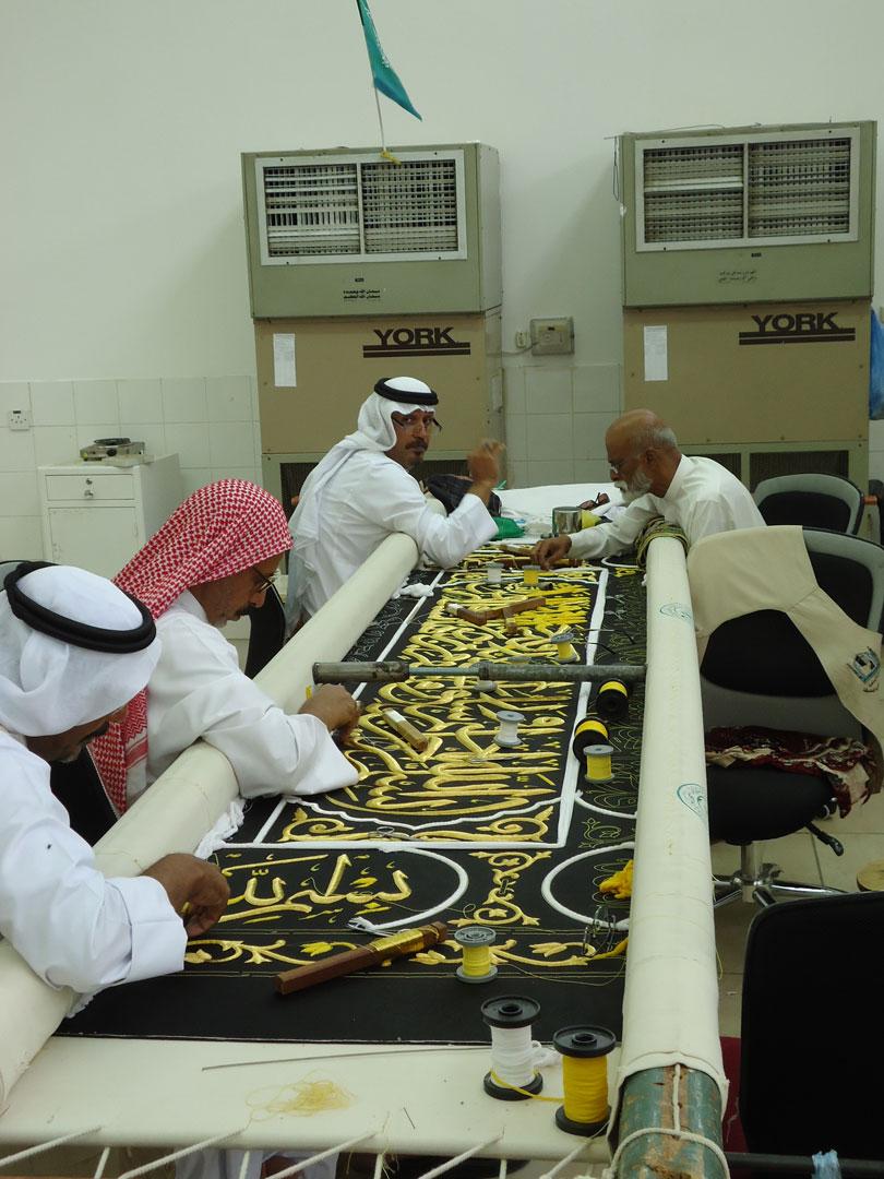Kâbe örtüsünün hazırlandığı atölye. Kur'an hattının en son katı altın ipliklerle işleniyor.